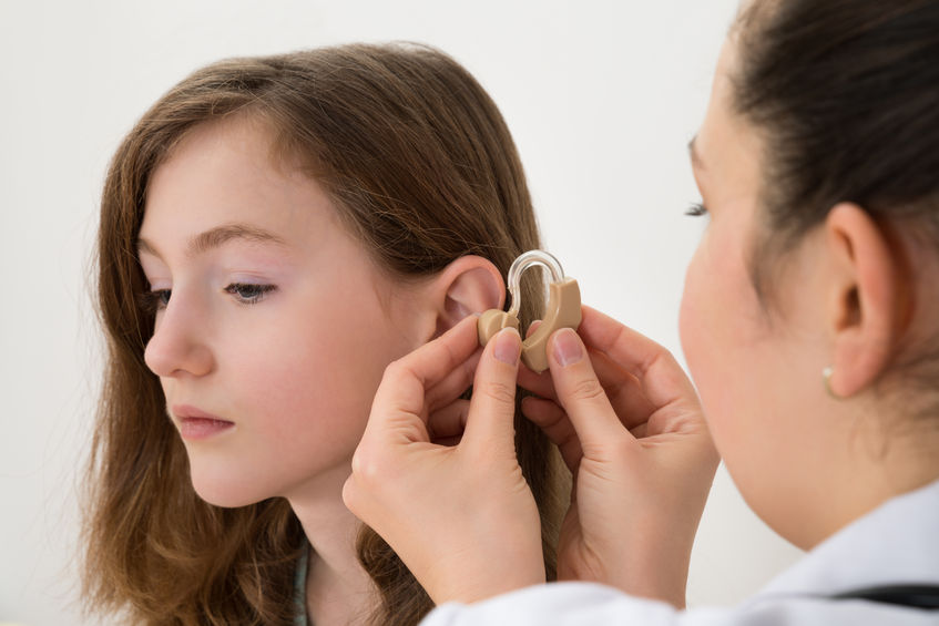 42611686 - close-up of doctor inserting hearing aid in the ear of a girl